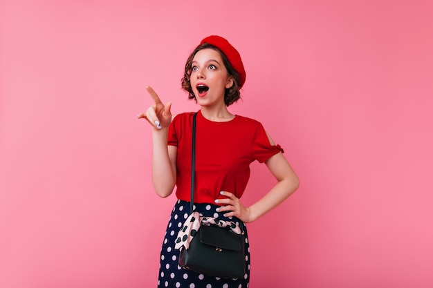 뭔가 흥미로운 것을 가리키는 손가락을 우아한 복장에 영감을 된 매력적인 여자. 프랑스 베레모와 빨간 블라우스에 열정적 인 백인 여자의 실내 샷.