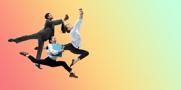 영감을 받은 행복한 회사원들은 그라데이션에 격리된 캐주얼 옷이나 정장을 입고 점프하고 춤을 춥니다.