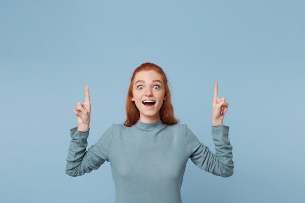 人差し指を上に向けて手を上げて目を大きく開いて口を持っているインスピレーションを得た楽しい赤毛の女性