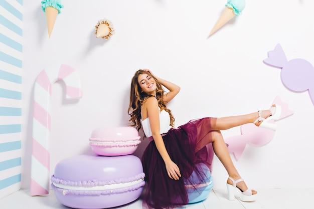 Вдохновленная смеющаяся девушка в модном пышном платье отдыхает на синем стуле с закрытыми глазами. довольно молодая леди в белых туфлях на каблуках, расслабляясь в комнате, украшенной печеньем и мороженым.