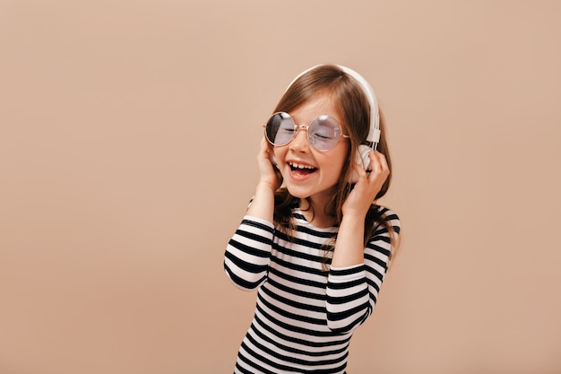 Inspired little girl in round violet glasses and stripped shirt has fun with closed eyes and broad smile