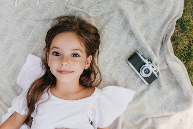 Piccola signora ispirata con grandi occhi marroni sdraiata su una coperta in giardino e alzando lo sguardo con un sorriso gentile. ritratto ambientale della ragazza dai capelli scuri in abito bianco rilassante per terra vicino alla telecamera.