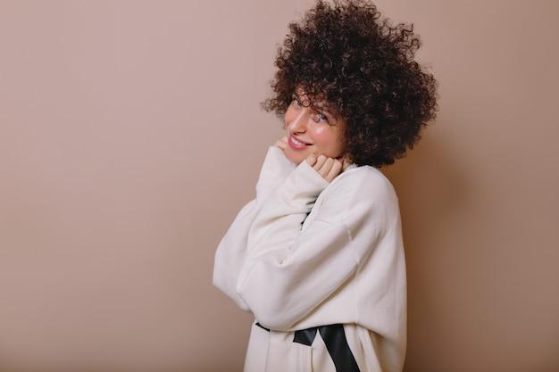 베이지 색에 포즈를 취하는 귀여운 풀오버에 웃고 영감을 얻은 사랑스러운 젊은 여성