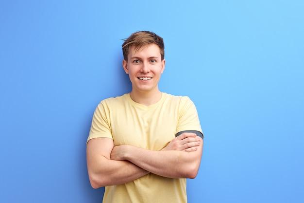 カジュアルなtシャツを着たインスピレーションを得た男性は、腕を組んで笑っています。青いスタジオの背景に分離。ライフスタイル、人々、人間の感情の概念
