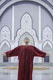 Вдохновленный мужчина в красном смотрит в небо с раскинутыми руками