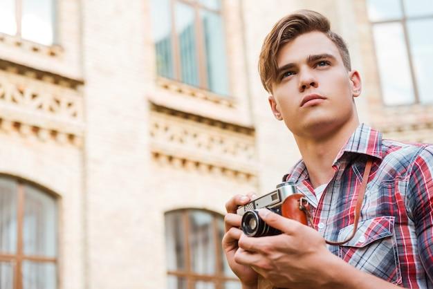 インスピレーションを得た写真家。ヴィンテージカメラを保持し、屋外に立っている間目をそらしているハンサムな若い男のローアングルビュー
