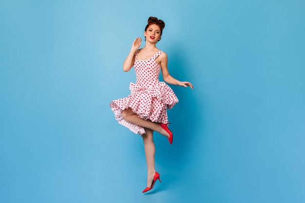 Inspired pinup girl with ginger hair standing on one leg. studio shot of elegant woman in polka-dot dress dancing on blue space.