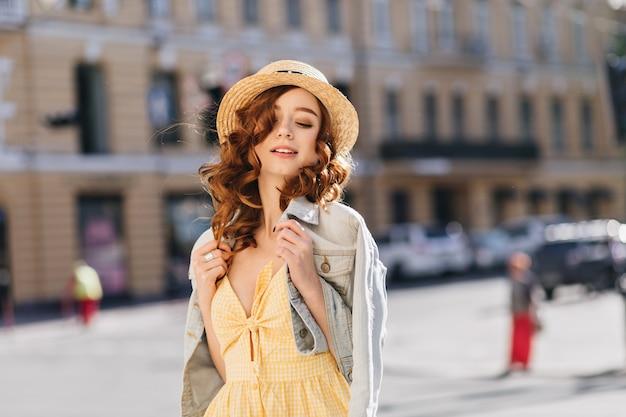 영감을받은 red-haired 젊은 여성이 여름 날에 도시를 탐험합니다. 우아한 모자에 사랑스러운 생강 여자의 야외 초상화.