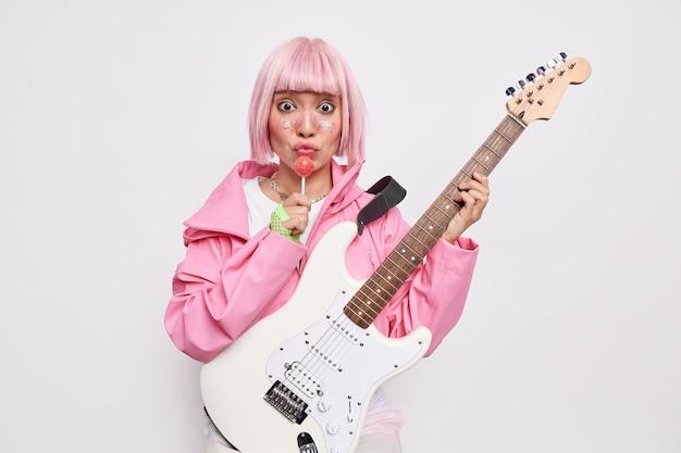 Вдохновленная рок-звезда с розовыми волосами держит леденец и акустическую гитару, одетая в куртку, делится музыкой с фанатами, одержимыми музыкой, берет уроки вокала