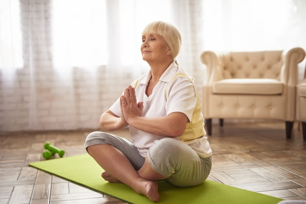 Inspired senior lady in lotus pose relaxing yoga.
