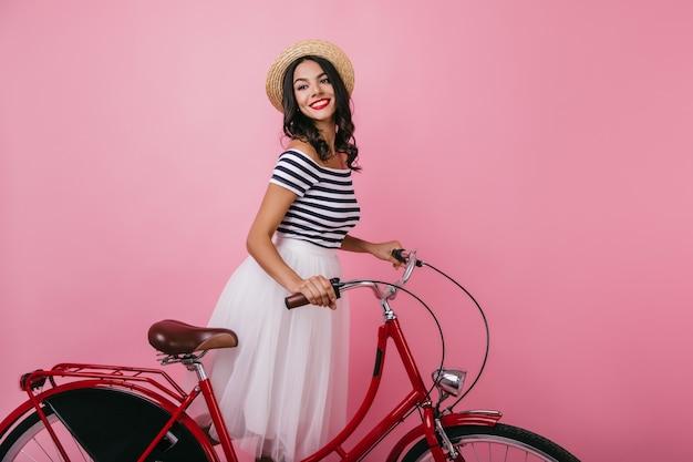 Ispirata donna formosa in piedi con la bicicletta e guardando lontano. beata ragazza dai capelli castani in cappello che gode del servizio fotografico dell'interno.