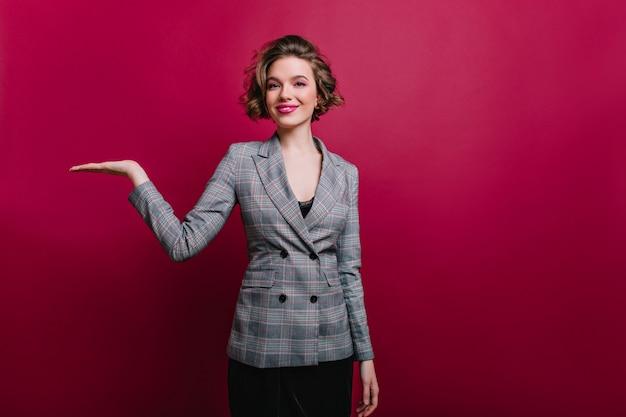 陽気な笑顔でポーズをとるエレガントなグレーのジャケットでインスピレーションを得たスリムな女の子。クラレットの壁で写真撮影を楽しんでいる短い巻き毛のかわいい実業家。