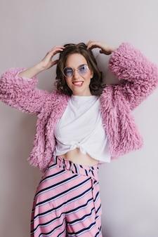 Вдохновленная стройная женщина в забавных очках играет с волосами на светлой стене. портрет удивительной темноволосой девушки в брюках с ремнями и шубе.