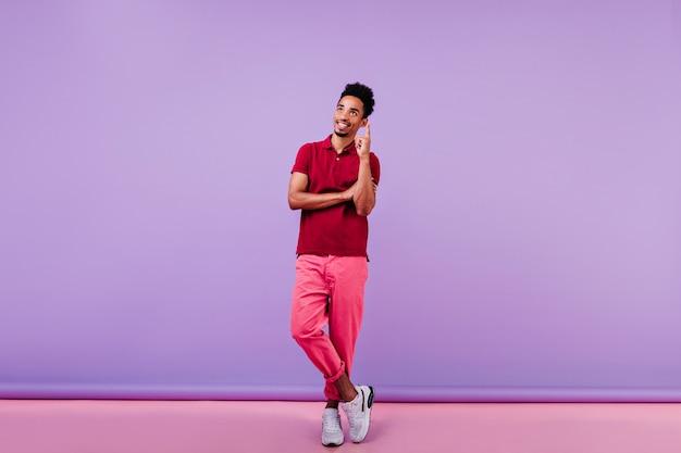실내를 즐기는 빨간 티셔츠에 웃는 남자 영감. 짧은 물결 모양의 머리에 서있는 잘 생긴 남자.