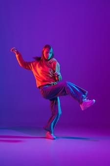 Вдохновленный. стильный спортивный мальчик танцует хип-хоп в стильной одежде на красочном фоне в танцевальном зале в неоновом свете. молодежная культура, движение, стиль и мода, действие. модный яркий портрет.