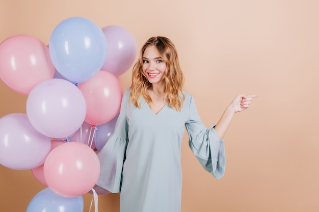 ヘリウム気球でポーズをとるインスピレーションを得た白い誕生日の女性