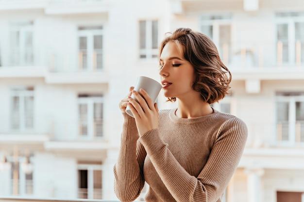 Ispirata signora bianca con acconciatura riccia che beve il tè. splendida giovane donna che gode del caffè nella fredda mattina d'autunno.