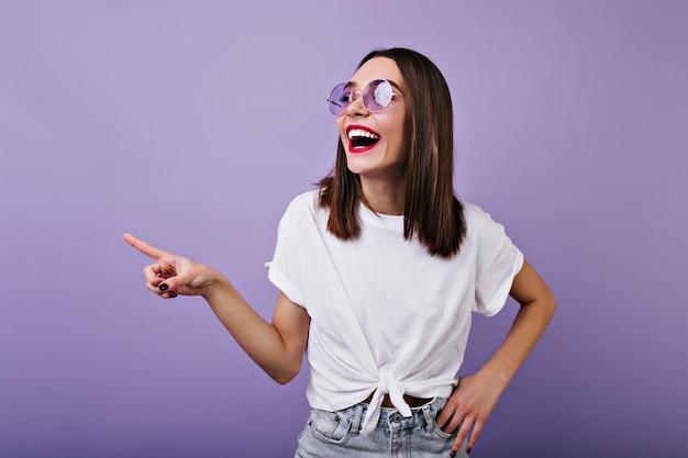 Вдохновленная белая женщина в солнечных очках, смеясь, смотрит в сторону.