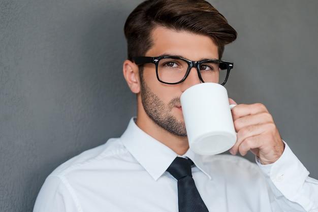 一杯の淹れたてのコーヒーからインスピレーションを得ています。コーヒーを飲むシャツとネクタイで自信を持って若い男