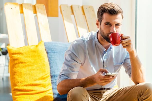 一杯の淹れたてのコーヒーからインスピレーションを得ています。携帯電話を持って、オフィスの休憩所に座ってコーヒーを飲むハンサムな若い男