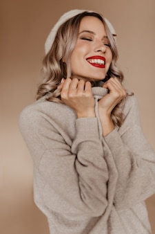 Inspired woman in cozy brown sweater posing with eyes closed