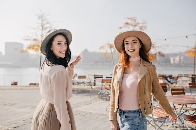 生姜の友人と一緒に歩いて、笑顔で肩越しに見ている白いブラウスのインスピレーションを得た女性