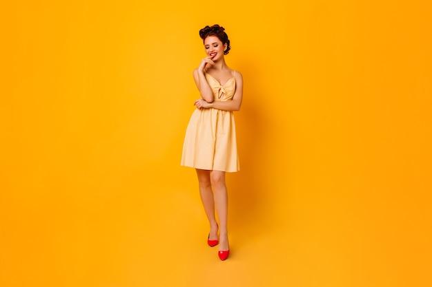 黄色い空間でふざけてポーズをとるインスピレーションを得た女性。写真撮影を楽しんでいるショートドレスの素晴らしいピンナップ女性。