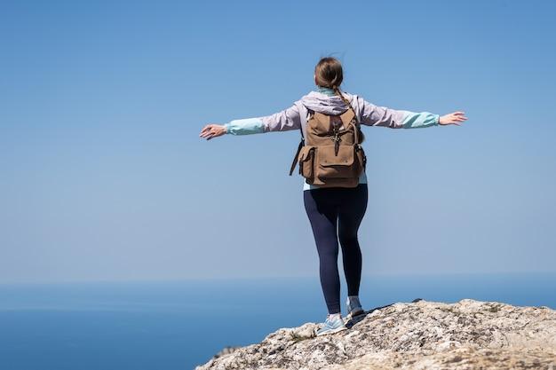 Вдохновленная женщина-путешественница раскинула руки в стороны и с большой высоты смотрит вдаль. чувство свободы и силы воли.