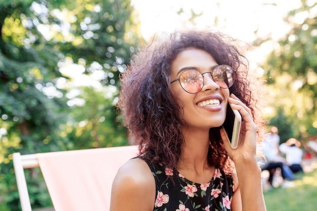 Donna ispirata con i capelli ricci che si rilassano nel parco di estate nel fine settimana soleggiato.