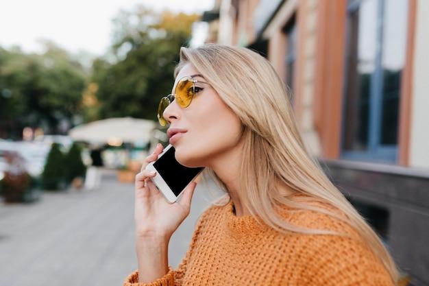 긴 금발 머리가 누군가에게 전화를 걸어 거리를 바라보고 영감을 얻은 여성