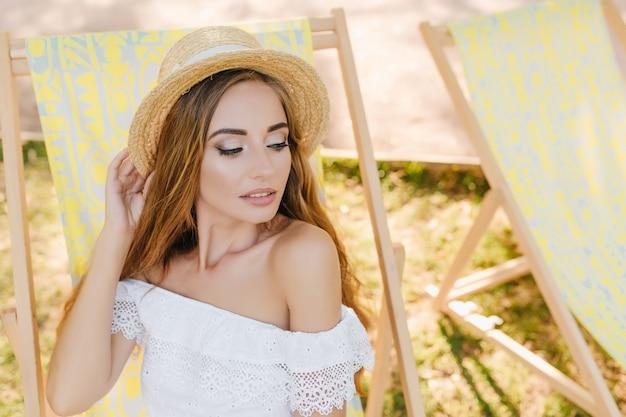 夏の日に黄色の長椅子に座って輝くメイクでインスピレーションを得た女性。トレンディな帽子とレースのドレスを見下ろす優雅な軽く日焼けした女の子の屋外の肖像画。