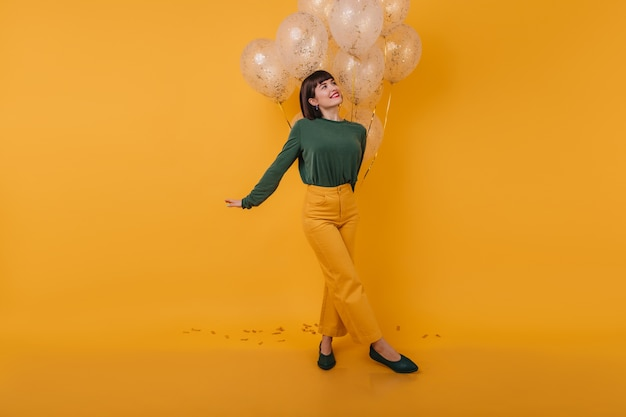 Inspired woman with trendy haircut looking away while posing with party balloons. indoor photo of amazing caucasian lady in vintage outfit having fun after party.