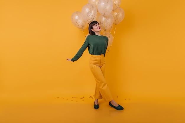 Вдохновленная женщина с модной прической смотрит в сторону, позируя с воздушными шарами. фотография в помещении удивительной кавказской дамы в винтажном наряде, развлекающейся после вечеринки.