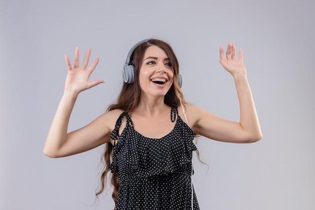 Вдохновленная молодая красивая девушка в платье в горошек, наслаждающаяся любимой музыкой через беспроводные наушники, смешные танцы