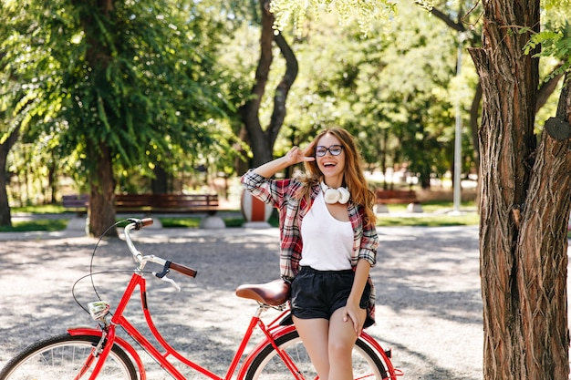 夏の公園で休んでいるカジュアルな服を着たインスピレーションを得た若い女性。彼女の自転車の近くでポーズをとっている眼鏡をかけた素晴らしいブロンドの女の子の屋外写真。