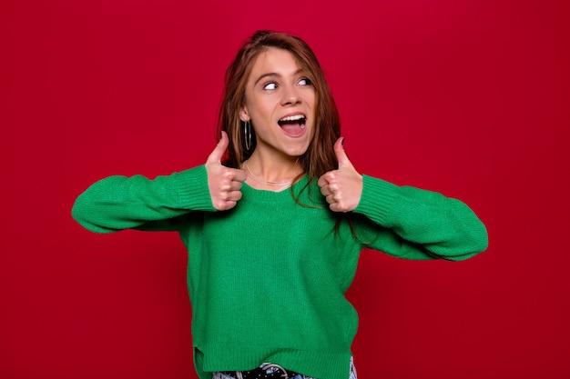 明るい茶色の長い髪の若い女性は、緑のセーターを着て、赤い背景の上に素晴らしい笑顔でポーズをとり、勝利の兆候を示しています