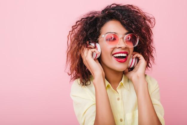 好きな曲を聴きながら笑う、薄茶色の肌を持つインスピレーションを得た若い女性。ヘッドフォンを保持しているカジュアルな快適な服装でクローズアップキャッチムラートの女性。