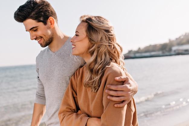 해변에서 산책하는 동안 여자 친구를 껴안은 젊은 남자 영감. 바다에서 주말을 보내는 호기심 금발 여자.