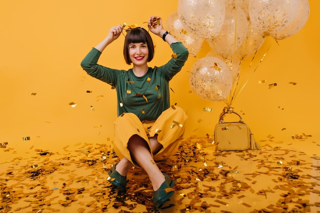 영감을받은 젊은 여성이 생일에 장난을 치고 있습니다. 풍선 바닥에 앉아 갈색 머리 매혹적인 여자의 실내 사진.