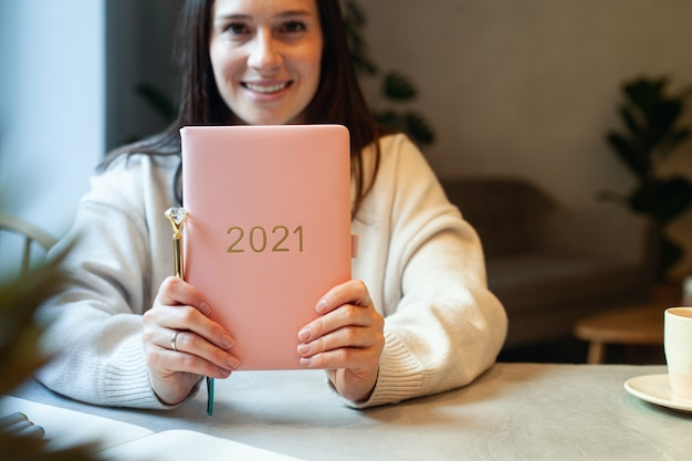 Вдохновленная молодая женщина с улыбкой смотрит в окно и держит дневник 2021 кораллового цвета. концепция надежды и вдохновения. леди улыбается и мечтает о будущем новом году. счастья и успехов.