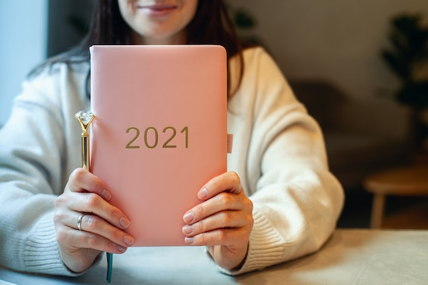 Inspired young woman with a smile looking through window and holding coral colored diary 2021