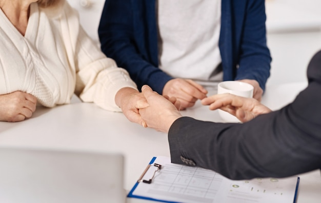 Inspiring confidence. sincere trustful elderly couple sitting at home and concluding agreement with real estate agent while shaking hands