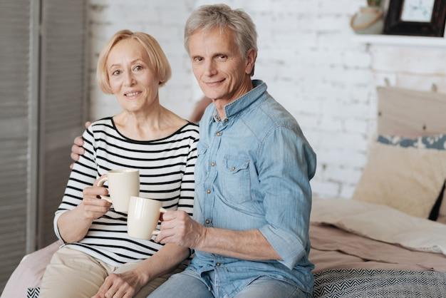 Вдохновляющая пара. очаровательная, полная энтузиазма милая семья, приятная беседа, делящий момент единства и попивая чай