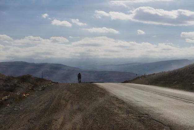 영감을 주는 자연, 길 위에 산과 하늘을 배경으로 한 남자가 있습니다.