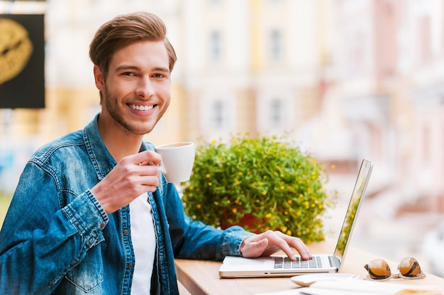 一杯の淹れたてのコーヒーで刺激を受けます。一杯のコーヒーを保持し、ラップトップに取り組んでいる若い男の笑顔