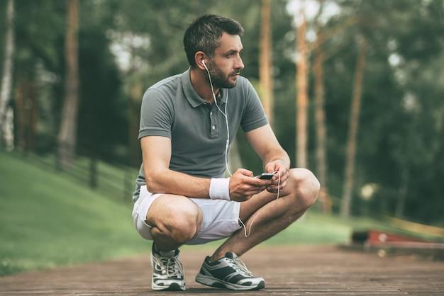 好きな音楽でインスピレーションを与えます。ヘッドフォンを着用し、公園でしゃがみながら目をそらしているスポーツウェアの思いやりのある若い男