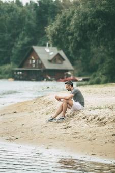 音楽と新鮮な空気に刺激を与えます。ヘッドフォンを着用し、川岸に座って目をそらしているスポーツ服を着たハンサムな若い男