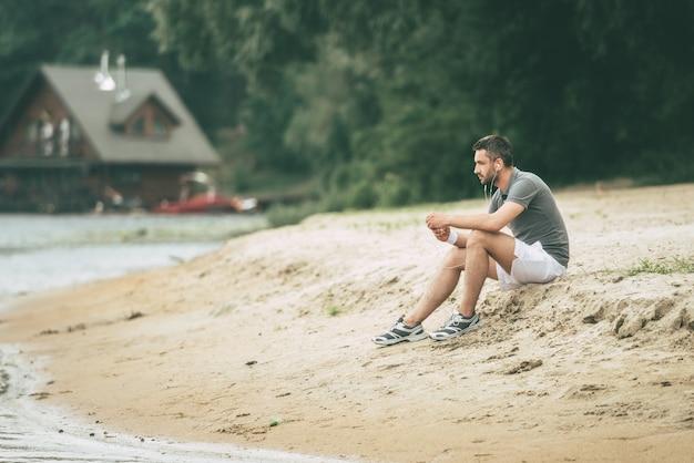 音楽に刺激を与える。ヘッドフォンを着用し、川岸に座って目をそらしているスポーツウェアの思いやりのある若い男