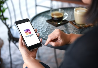 Instagram application on smart phone display in hand with coffee on table background