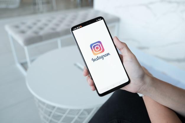 Instagramアプリケーションのログイン画面を持つスマートフォンを持つ女性の手。 instagramは最大かつ最も人気のある写真ソーシャルネットワーキングです